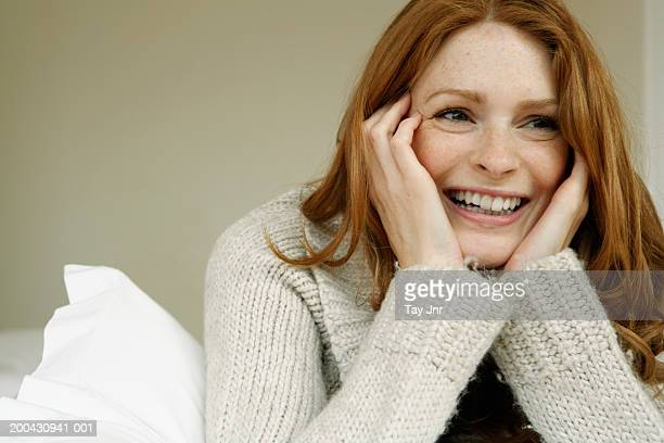 Young woman lying on bed, resting head in hands, laughing, close-up