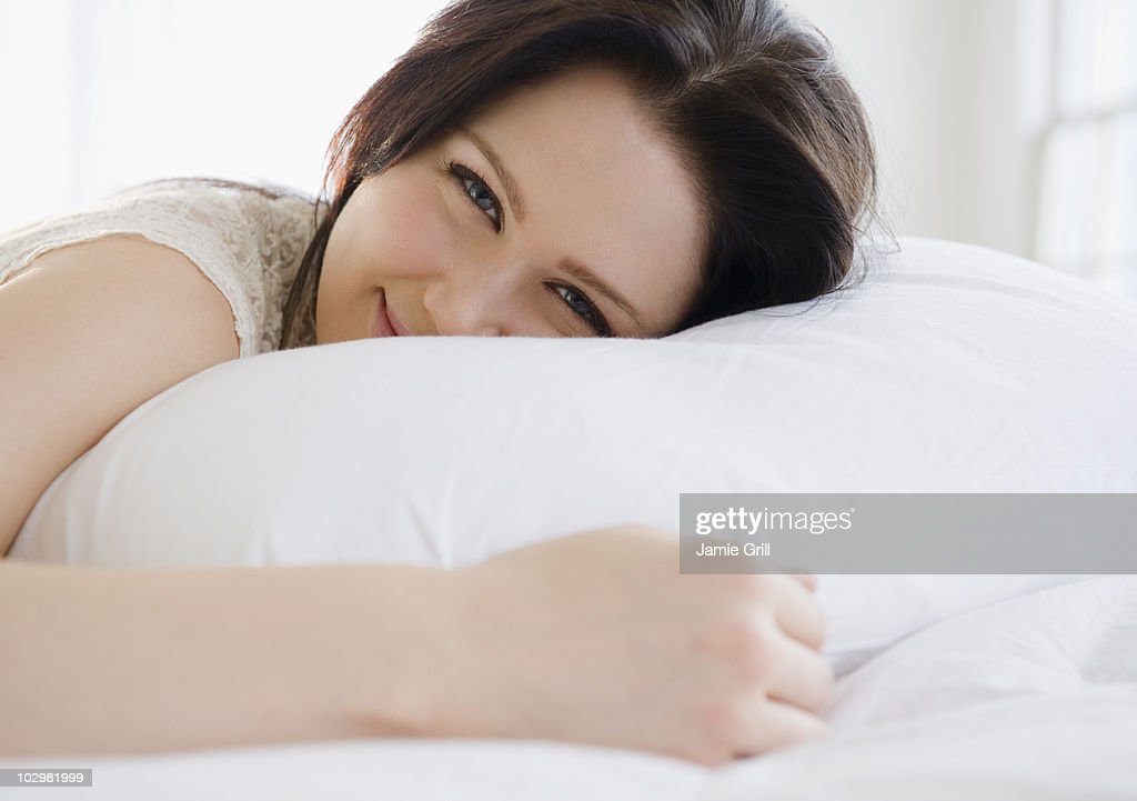 Young woman lying on bed, smiling : Stock Photo