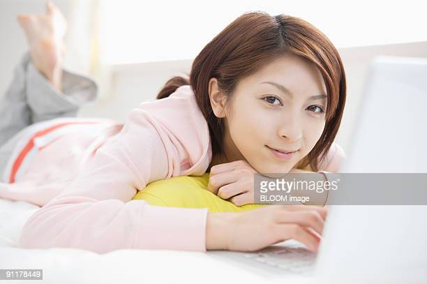 Young woman lying on bed using laptop PC