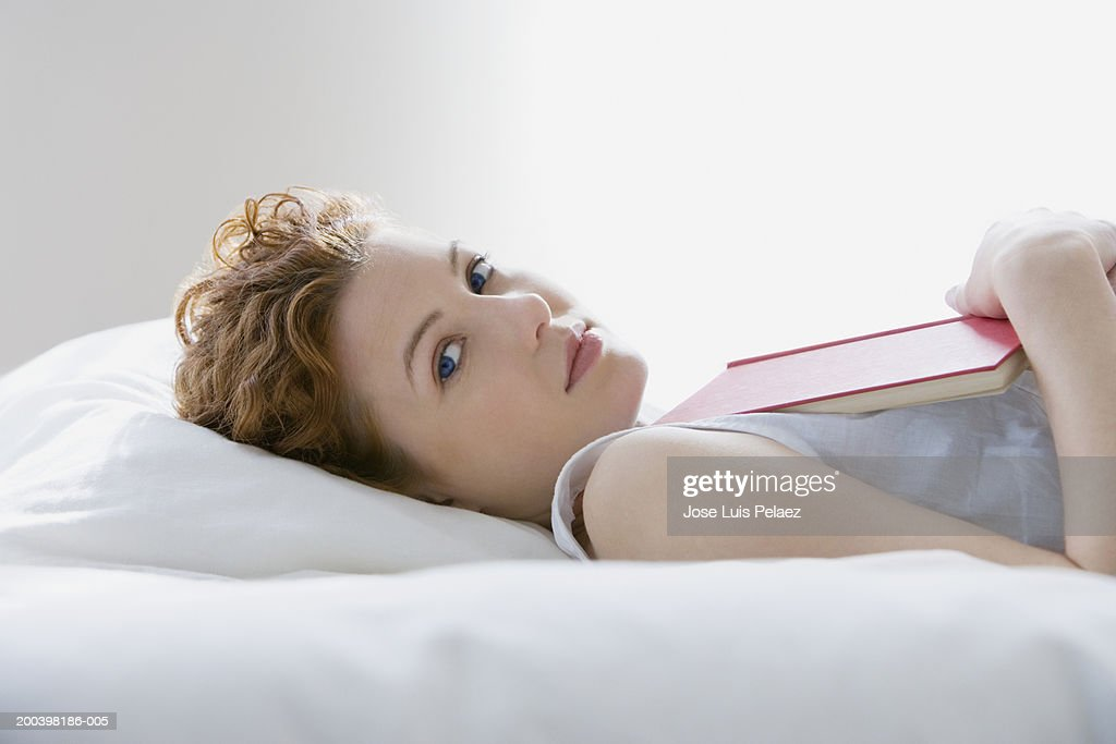 Young woman lying on bed with book, portrait, close-up