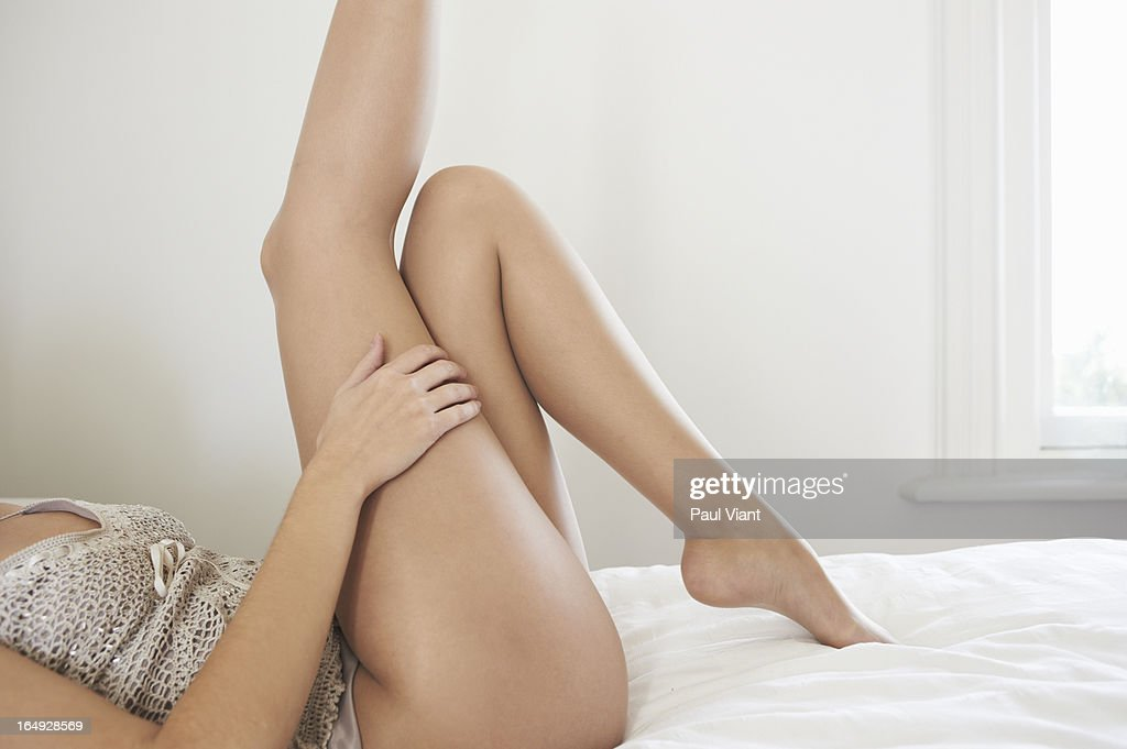 Young woman lying on bed with legs in air