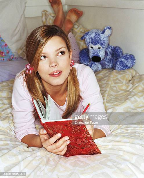 Young woman lying on bed, writing in journal