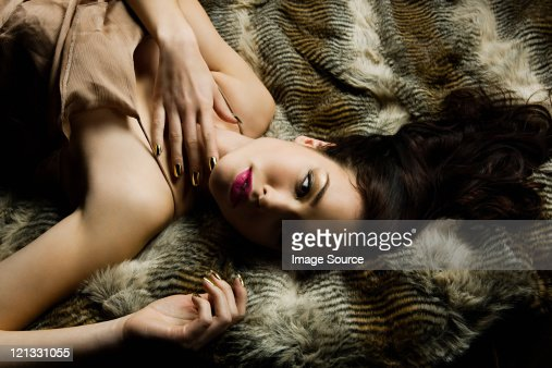 Young woman lying on blanket, portrait