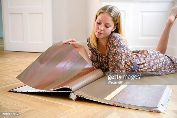 Young woman lying on floor selecting wallpaper from a catalogue