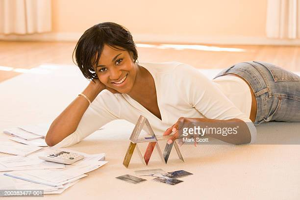 Young woman lying on floor, stacking credit cards