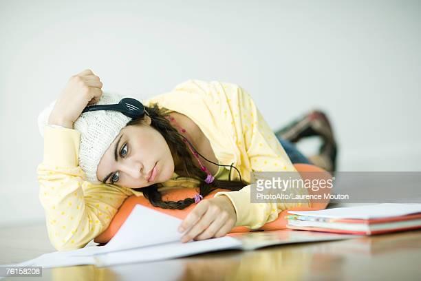 'Young woman lying on floor, wearing headphones and studying'