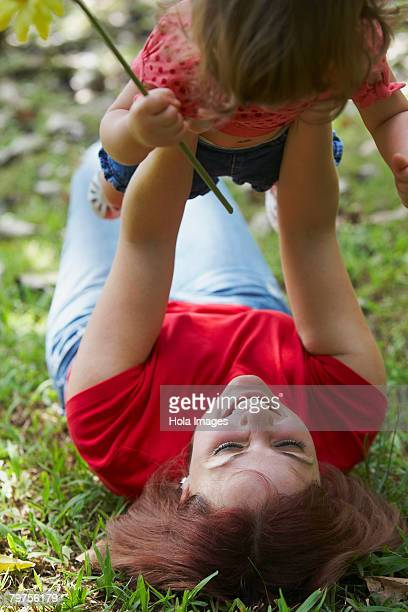Young woman lying on grass and picking up her daughter