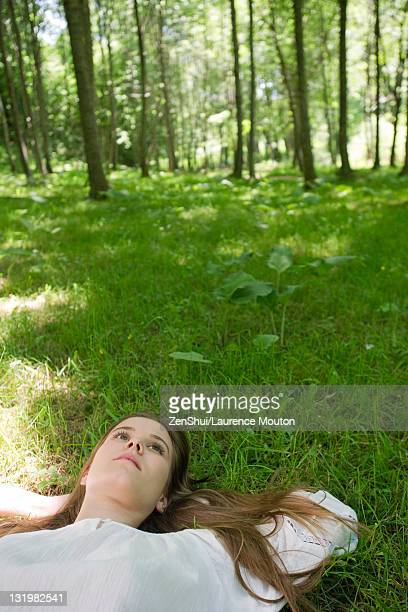 Young woman lying on grass daydreaming
