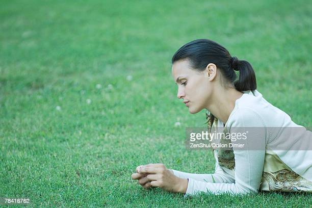 Young woman lying on grass, holding blade of grass in fingers