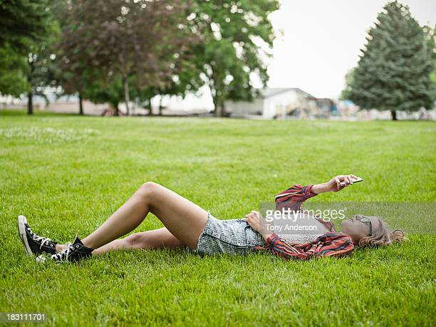 Young woman lying on grass in park with mobile