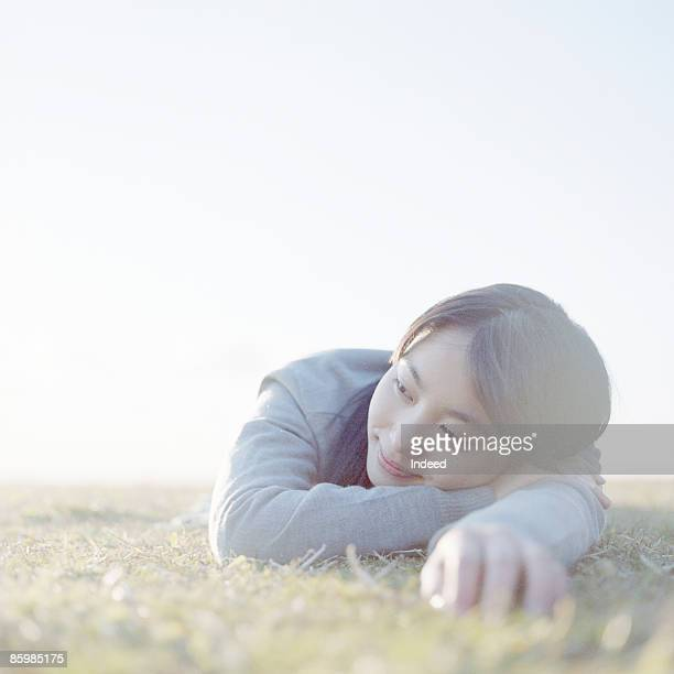 Young woman lying on grass, looking away