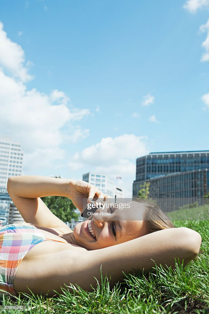Young woman lying on grass talking on phone : Stock Photo