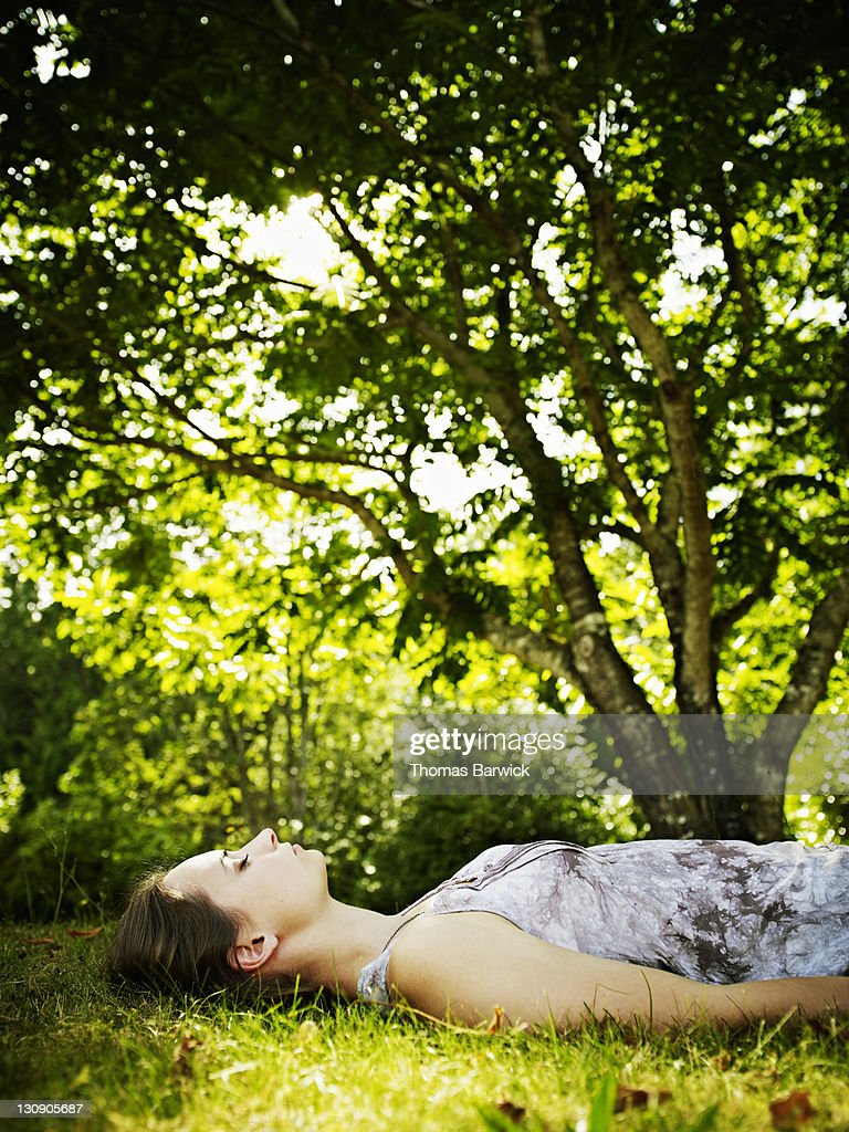 Young woman lying on grass under tree eyes closed : Stock Photo