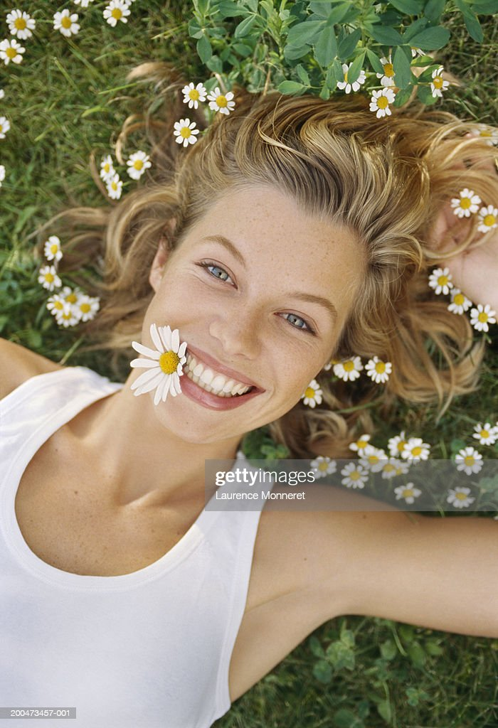 Young woman lying on grass, with daisy in mouth, smiling, portrait