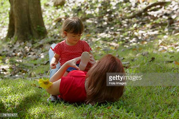 Young woman lying on grass with her daughter sitting on her stomach