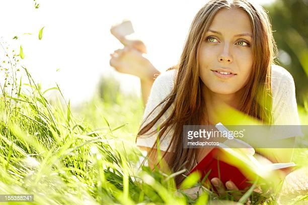 Jeune femme allongée sur l'herbe avec bloc-notes et un stylo