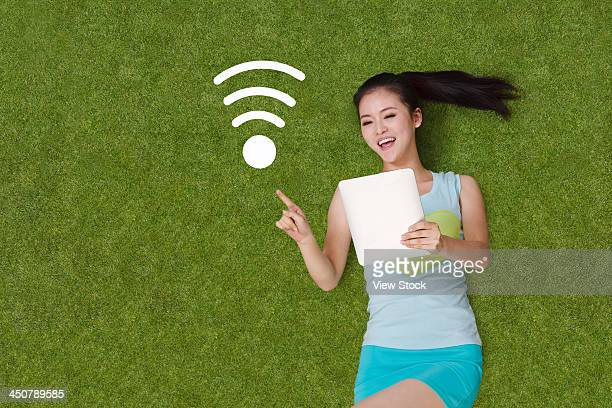 Young woman lying on grass with tablet