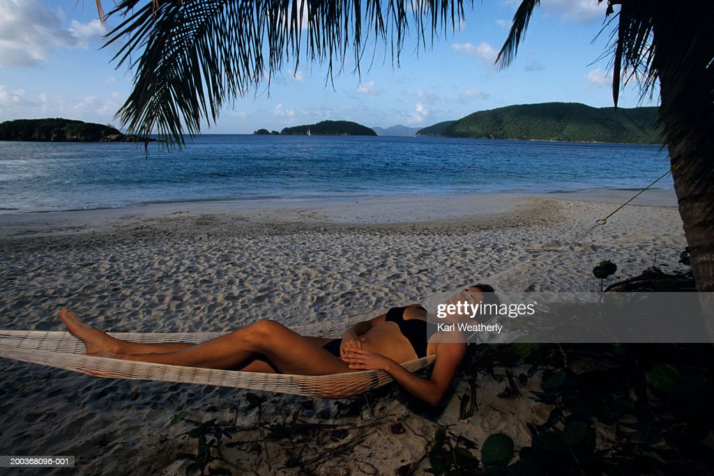 Young woman lying on hammock in shadow of palm trees : Stock Photo