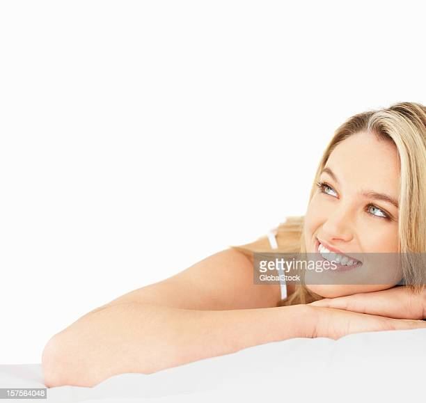 Young woman lying on her stomach and smiling
