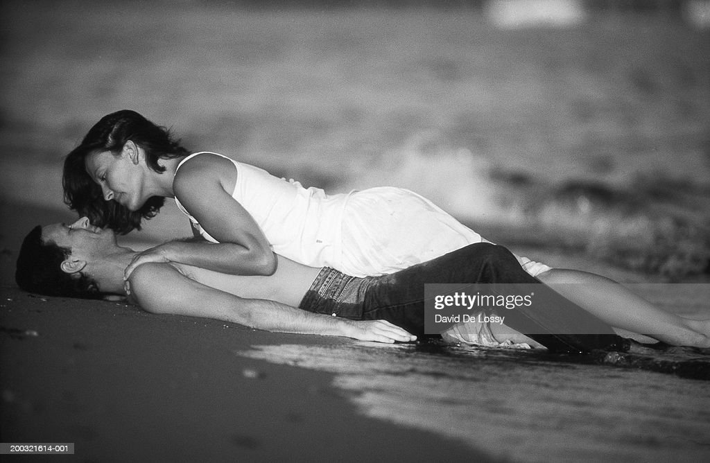Young woman lying on man at beach (B&W) : Stock Photo