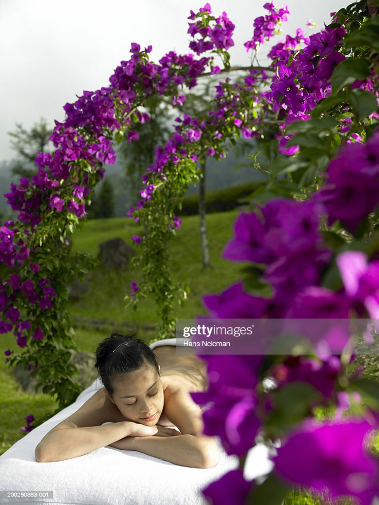 Young woman lying on massage table at spa : Stock Photo