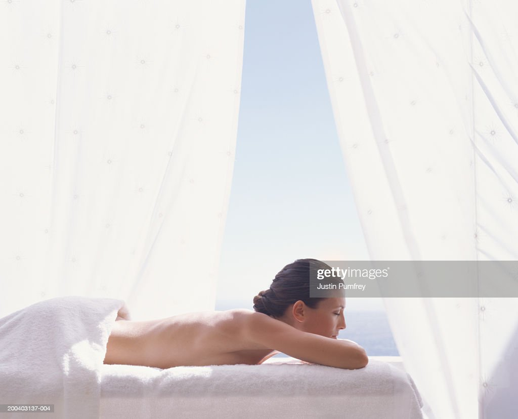 Young woman lying on massage table, eyes closed, profile : Stock Photo