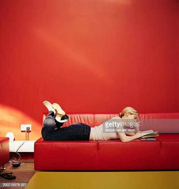 Young woman lying on red sofa reading