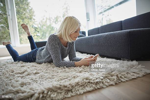 Young woman lying on rug using cell phone