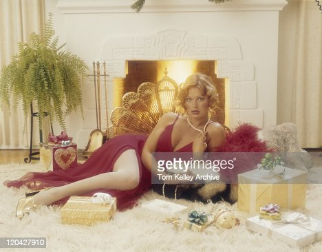 Young woman lying on rug with gift in front of fireplace, portrait : Stock  Photo - Young Woman Lying On Rug With Gift In Front Of Fireplace Portrait