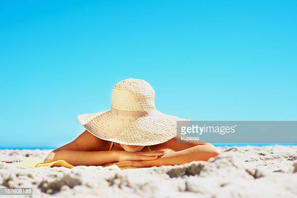 Young woman lying on sandy beach