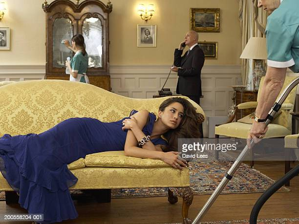 Young woman lying on sofa and maids vacuuming room