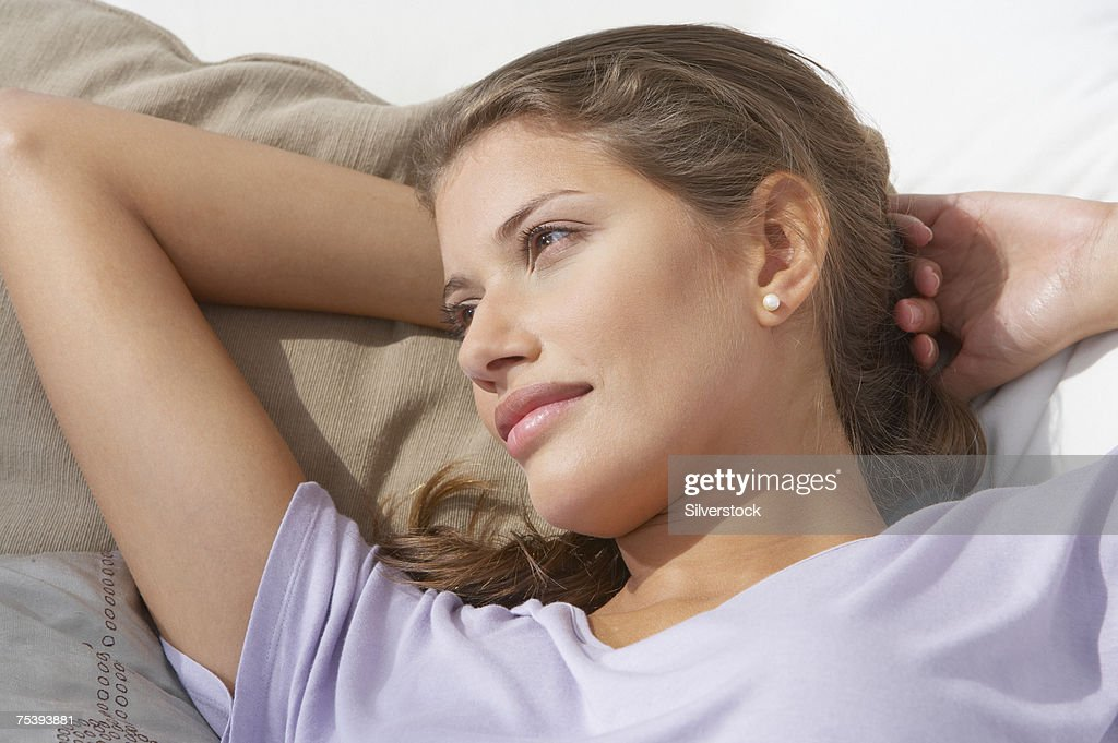 Young woman lying on sofa, close-up : Stock Photo