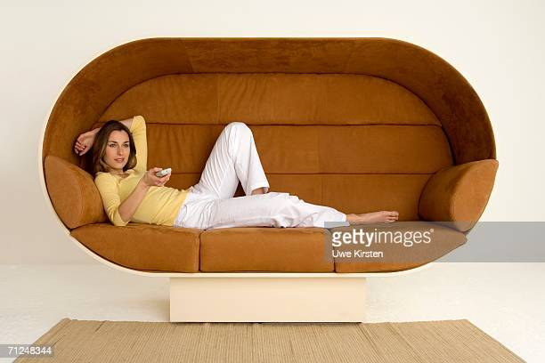 Young woman lying on sofa holding remote control, smiling