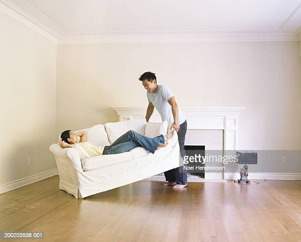 Young woman lying on sofa, man lifting one side of sofa off floor