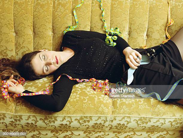 Young woman lying on sofa strewn with party streamers, eyes closed