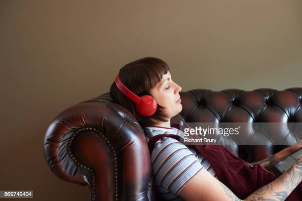 Young woman lying on sofa with headphones listening to music
