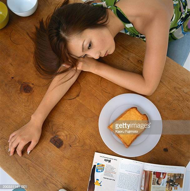 Young woman lying on table, overhead view