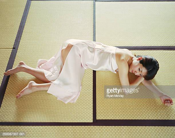Young woman lying on tatami mats, elevated view