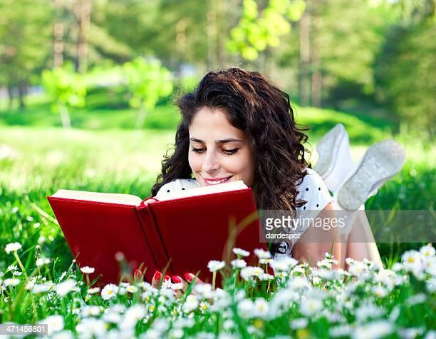 Giovane donna sdraiata sull'erba e leggendo
