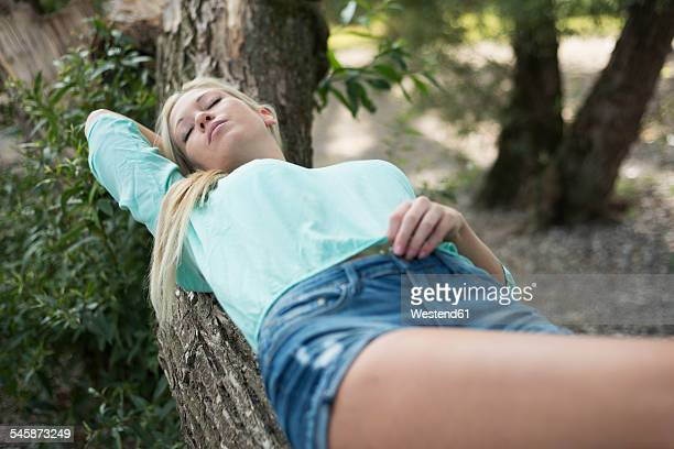 Young woman lying on tree trunk having a rest
