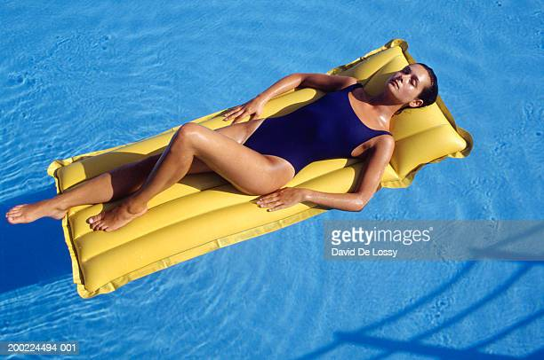 Young woman lying on yellow airbed, elevated view