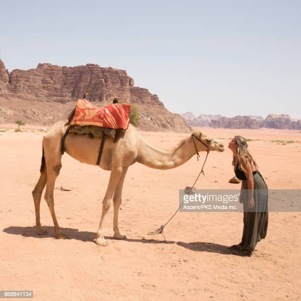 Young woman makes contact with camel in desert landscape