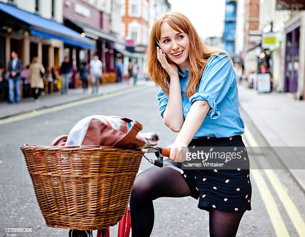 Young woman makes phone call on bike