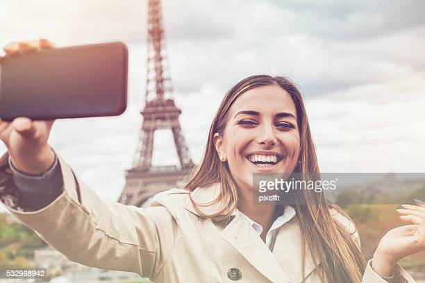 Young woman making a selfie with the Eiffel Tower