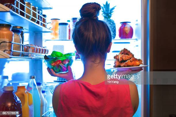 Young Woman Making Choices for a Healthy Salad or Junk Food Fried Chicken