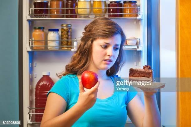 Junge Frau, die Entscheidung über gesunde Ernährung vor Kühlschrank