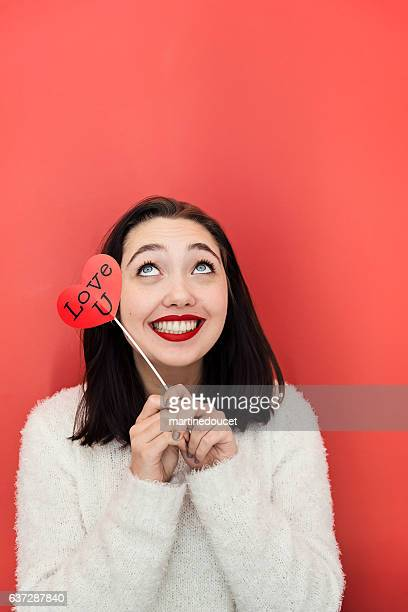 Young woman making faces with props on red wall.