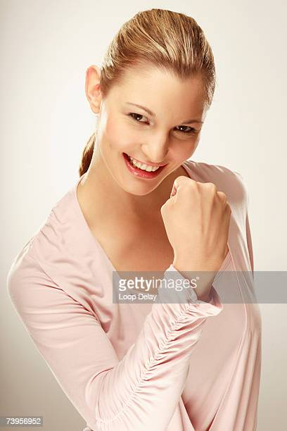 Young woman making fist, smiling, portrait