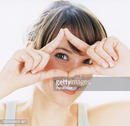 Young woman making frame with hand, smiling, portrait, close-up : Stock Photo