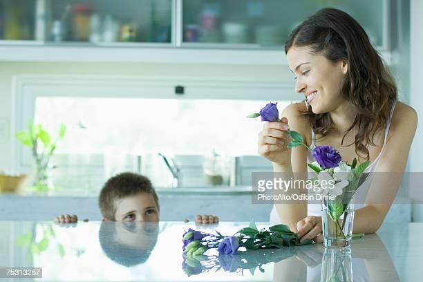 Young woman making fresh flower arrangement, smiling at boy